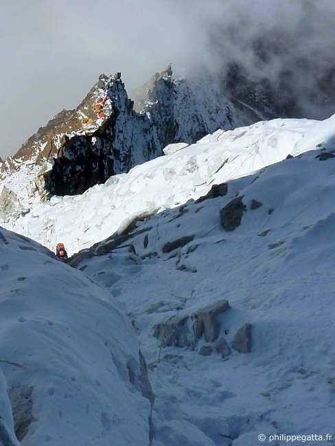 Jean-Marc in the mixed terrain at around 6100 m, C2 behind (Photo � P. Gatta)